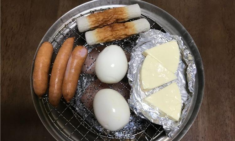 上の段の網をセットし、チーズ、卵、ちくわ、ウィンナーをのせた