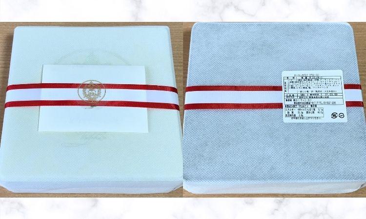 白い不織布に包まれ、赤いリボンが巻かれているクッキー缶