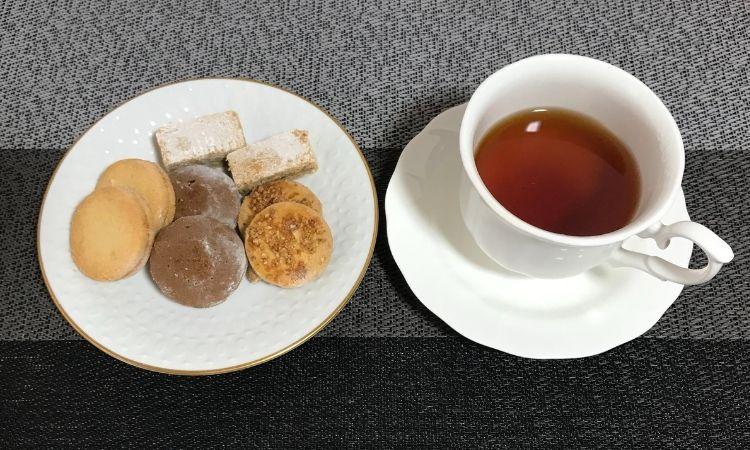 左にはクッキーがお皿にのせられている。右はカップに入れた紅茶。