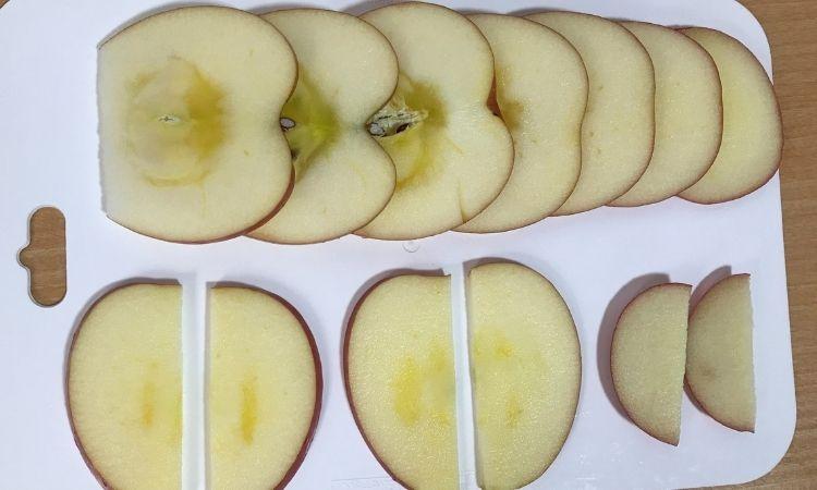 りんごを縦に薄く切り、さらに半分に切った画像