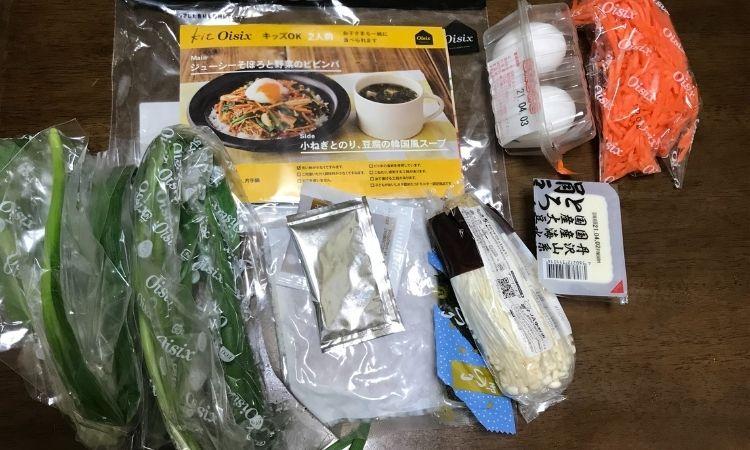 kitOisix主菜「ジューシそぼろと野菜のビビンバ」副菜「小ネギとのり、豆腐の韓国風スープ」2人前を袋から出した状態。人参やネギ、豆腐卵など入っている。