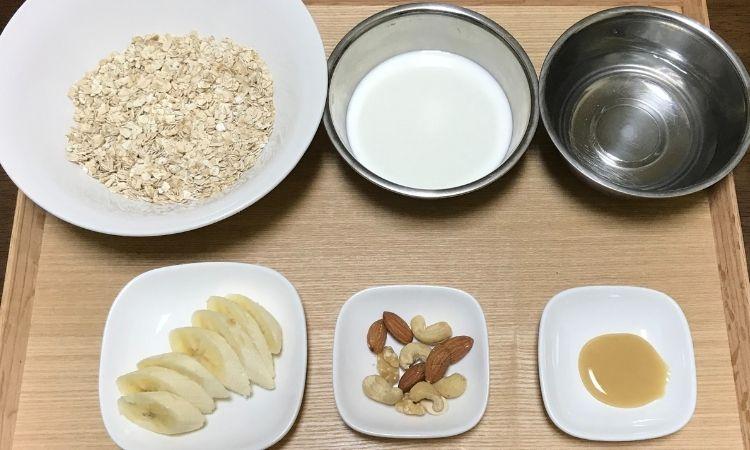オートミール、牛乳、水、バナナ、ミックスナッツ、はちみつを並べた画像