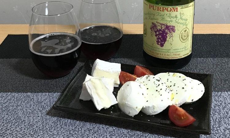 お皿にオリーブオイルと塩コショウがかかったチーズ、トマト。グラスに注がれたピュアポムのレッドと、ボトル