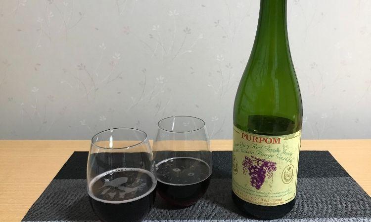 ピュアポムスパークリングジュースレッドのボトル、グラスに注がれたレッドジュース