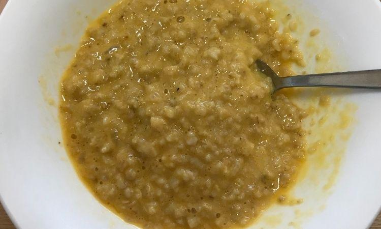 加熱したオートミールに生卵を加えてスプーンで混ぜている画像