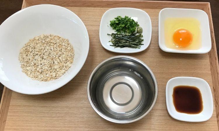 オートミール卵かけご飯に必要な食材、オートミール、水、生卵、醤油、薬味のネギ、海苔、わさびが並べられている。