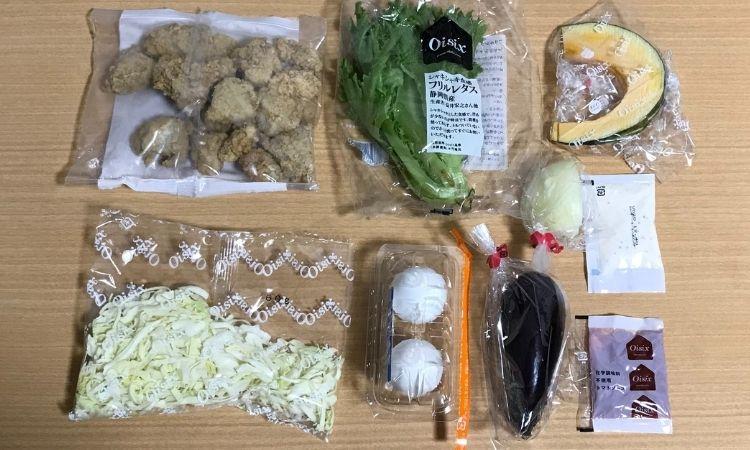 キットの中身を並べた画像。唐揚げ、レタス、キャベツ、玉ねぎなどの野菜、ゆで卵、調味料が並べられている