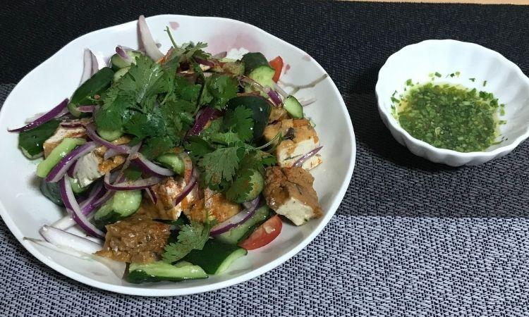 「「パクチー香る、生揚げのエスニックサラダ」をお皿に盛り付け、隣にパクチードレッシングが置いてある。