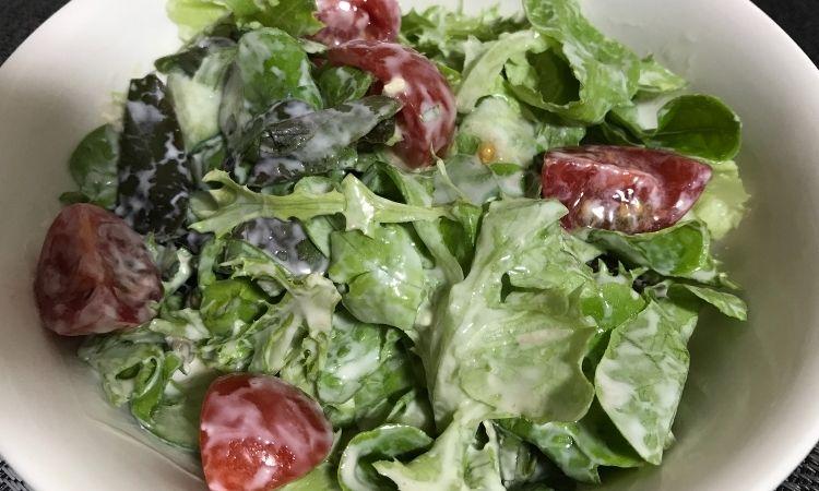 サラダとクリームチーズソースをよく和え皿によそった画像